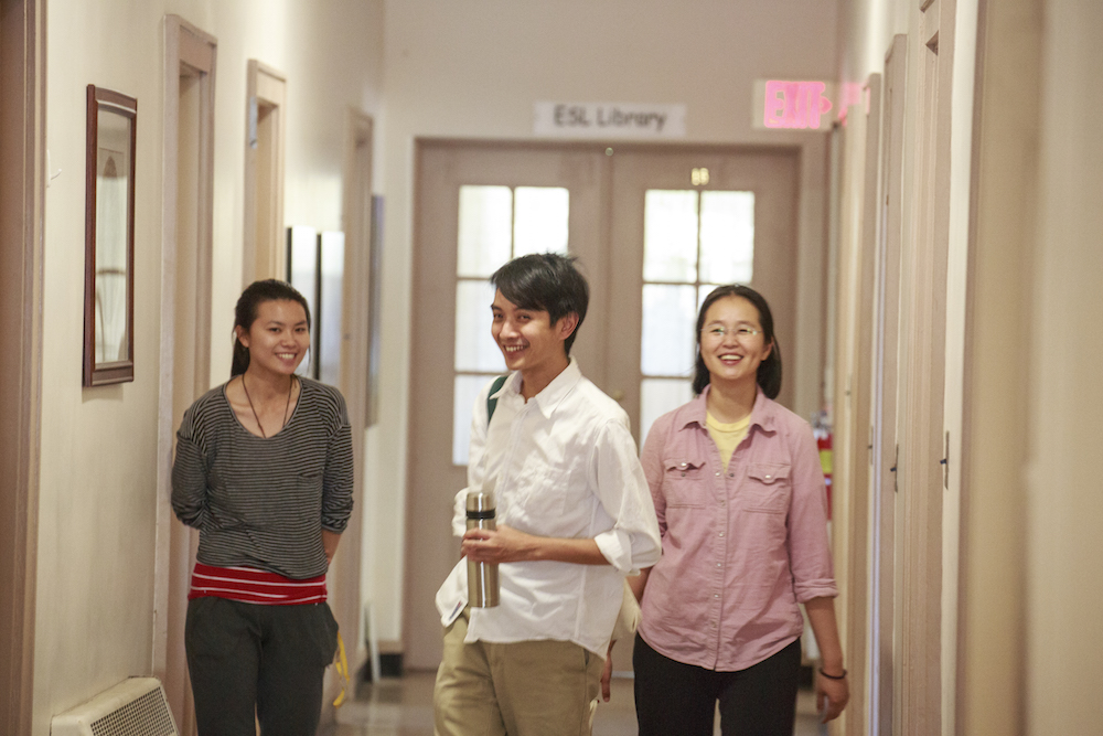 Three people laughing in a hallway in DRBU