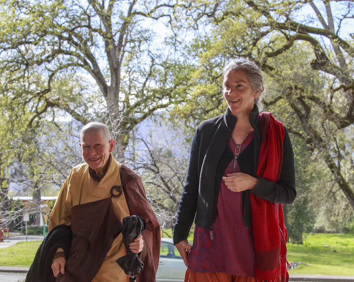 Two smiling students; one laity, one monastic, standing