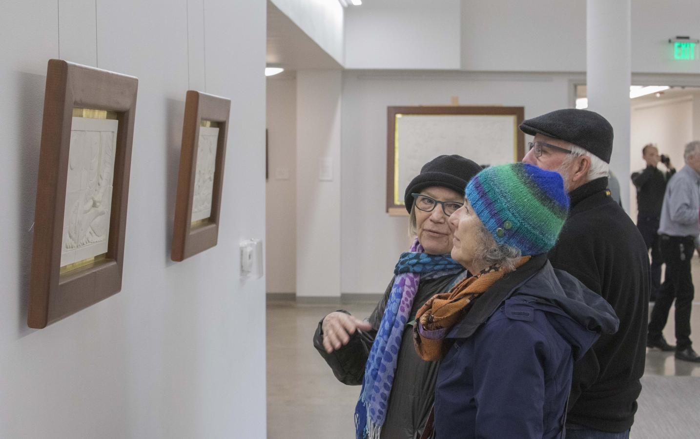 Visitors discuss ceramic reliefs at the opening of Śākyamuni Buddha: A Story, February 16