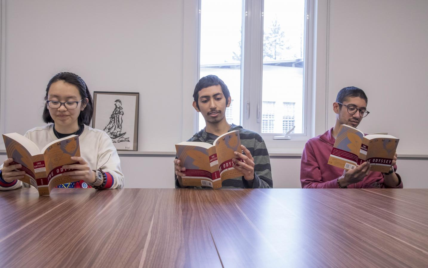 DRBU students reading a book in class